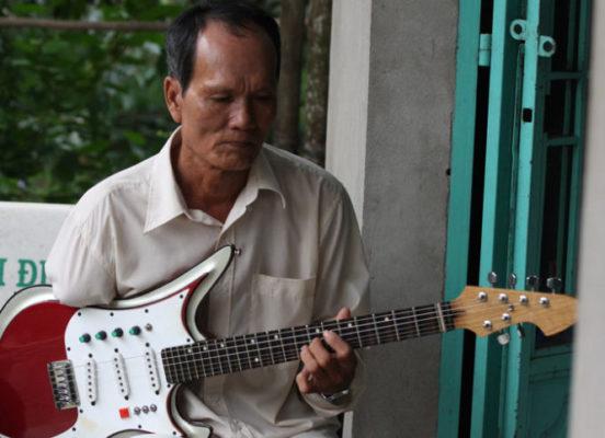 Ông Hai Cụt độc tấu đờn ghita phím lõm chỉ với tay trái - Ảnh: V.Tr.